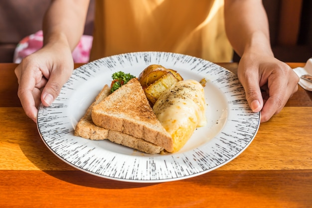 Woman hand holding white plate with omelet potato, tomatoes parsley and feta cheese Premium Photo
