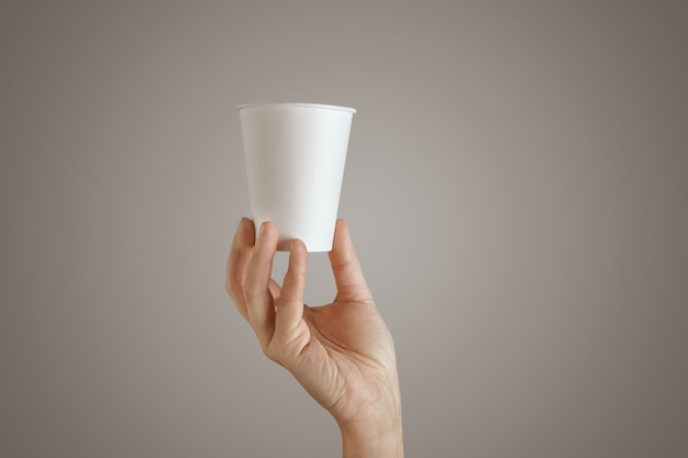 女性の手は空白の空のテイクアウト紙ガラスを下から保持、中央のプレゼンテーション、側面図、孤立した、認識できない 無料写真