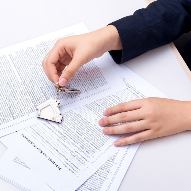 Woman hand and home key. signed contract and keys of the property with documents. Premium Photo