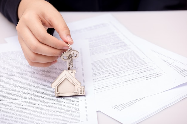 Woman hand and home key. signed contract and keys of the property with documents Premium Photo