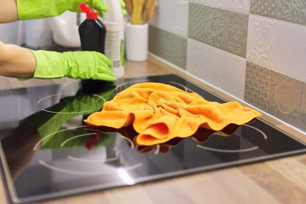 手袋をはめた女性の手がキッチンの電気セラミックコンロを掃除し、マイクロファイバークロスでガラスを磨く Premium写真