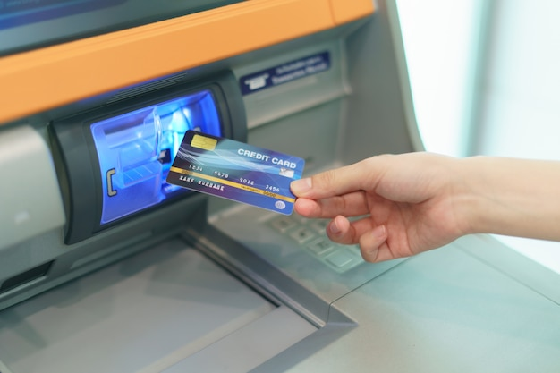 Woman hand  inserting a credit card, into bank machine to withdraw money at  automated teller machine( atm ). Premium Photo