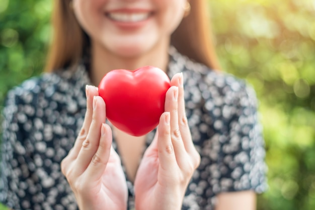 Woman hand is holding red heart Premium Photo