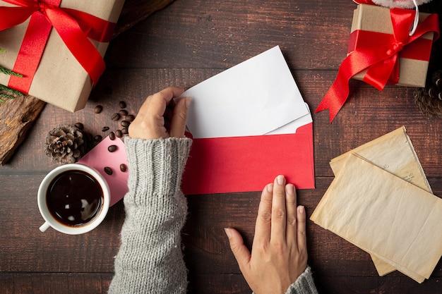 여자 손으로 봉투에 인사말 카드를 걸고있다 무료 사진