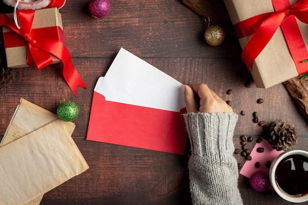 Woman hand is putting greeting card into envelope Free Photo