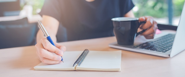 Woman hand is writing on a notebook with a pen in office.web banner. Premium Photo