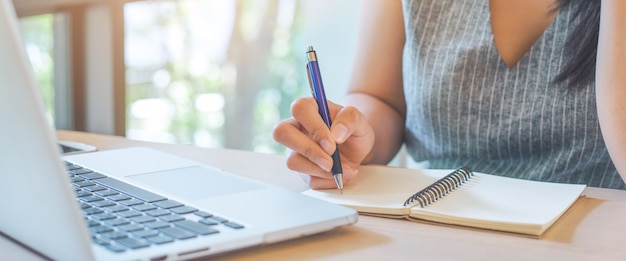 Woman hand is writing on notepad with pen in office. Premium Photo