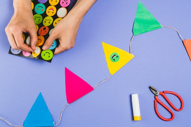 Woman hand making bunting with emoji stickers over colored background Free Photo