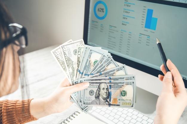 Женщина руки деньги с графиком на экране компьютера Premium Фотографии