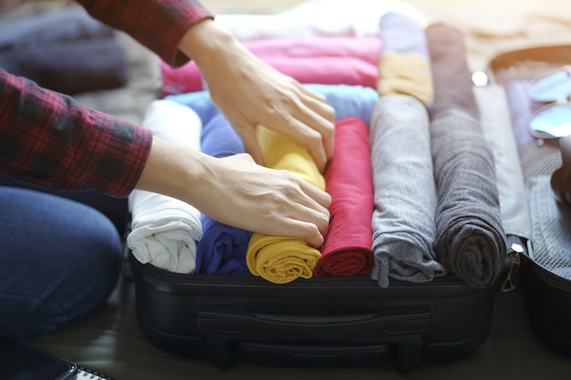 Woman hand pack clothes in suitcase bag on bed Premium Photo