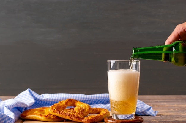 Woman hand pouring beer on wooden table. Premium Photo