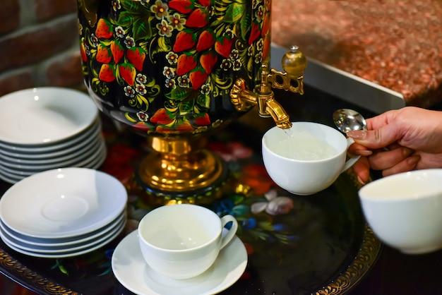女性の手がサモワールからお茶を注ぐ Premium写真