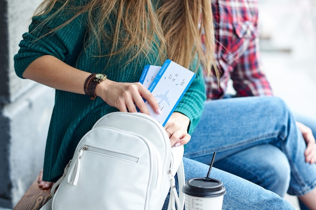 女性の手はバッグに搭乗券を置きました。チケットを持っている手。飛行機と旅行を待っています Premium写真