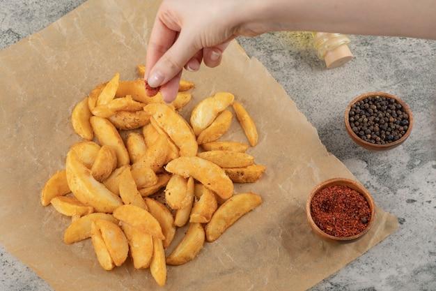 기름이 안 배는 종이에 튀긴 감자에 고추 가루를 넣어 여자 손. 무료 사진