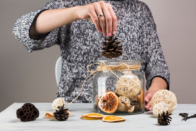 Woman hand putting pinecone in glass jar Free Photo