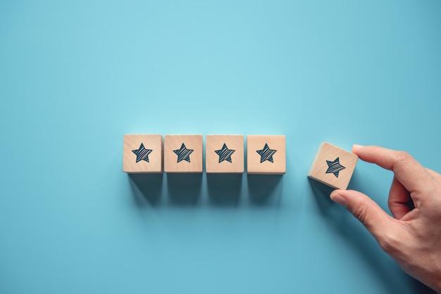 青の背景に木製の5つ星の形を置く女性の手。最高の優れたサービスの評価顧客体験のコンセプト、満足度。 Premium写真