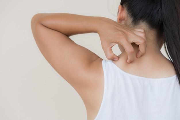 女性の手は、首と背中で手でかゆみを引っかく。ヘルスケアと医療のコンセプト。 Premium写真