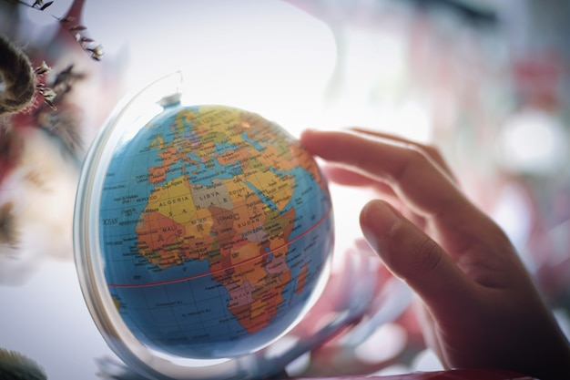 Woman hand select destination on the world map globe ball photo woman hand select destination on the world map globe ball premium photo gumiabroncs Choice Image