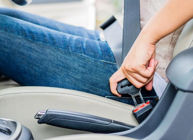 Woman hand sitting inside car fastening seat belt. safety belt safety first. Premium Photo