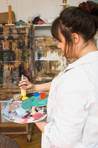 Woman hand squeezing yellow paint tube on messy painting palette Free Photo