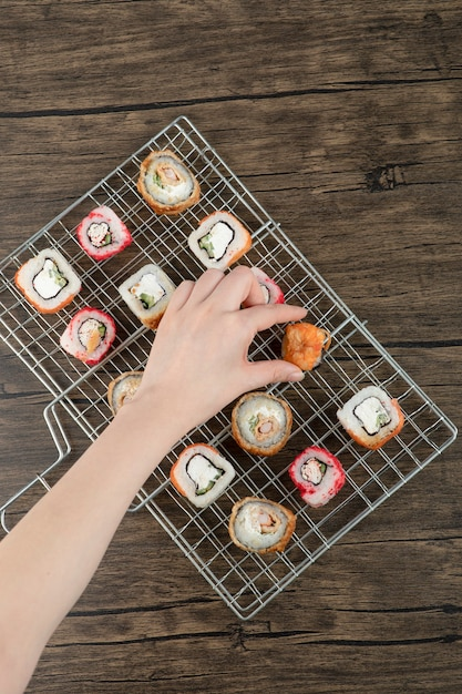 Woman hand taking one sushi roll from grilled basket on a wooden background . Free Photo