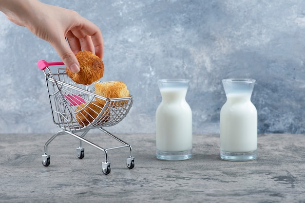 작은 핑크 카트에서 달콤한 과자를 복용하는 여자 손 대리석 테이블에 배치. 무료 사진