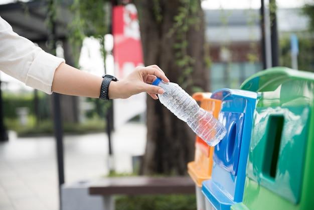 Woman hand throwing empty plastic water bottle in recycling bin. Premium Photo