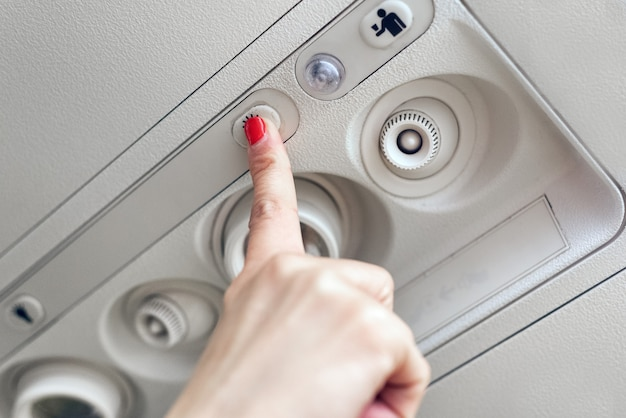 Woman hand up to adjust console panel at the air conditioner above the seat in cabin of low cost commercial airplane. Premium Photo