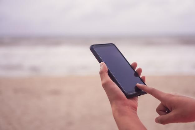 여자 손은 스마트 폰을 사용하여 비즈니스, 소셜 네트워크, 커뮤니케이션을 공개적으로 수행합니다. 프리미엄 사진