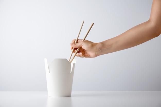 여자 손은 흰색 소매 세트 프리젠 테이션에 고립 된 테이크 아웃 빈 상자에서 맛있는 국수를 집어 젓가락을 사용 무료 사진