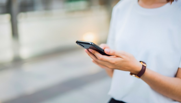 Woman hand using black smartphone. the concept of using the phone is essential in everyday life. Premium Photo