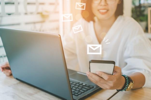 ラップトップコンピューターを使用してビジネスのメールを送受信する女性の手。 Premium写真