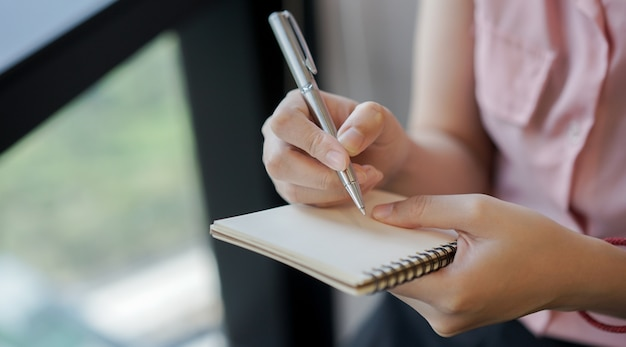Woman hand using pencil and writing on notebook Premium Photo