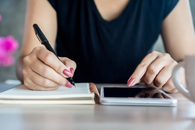 Woman hand using smart phone studying online Premium Photo