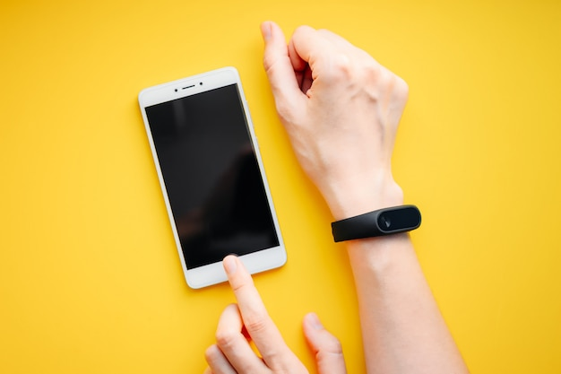 Woman hand with fitness tracker and smartphone on a yellow Premium Photo