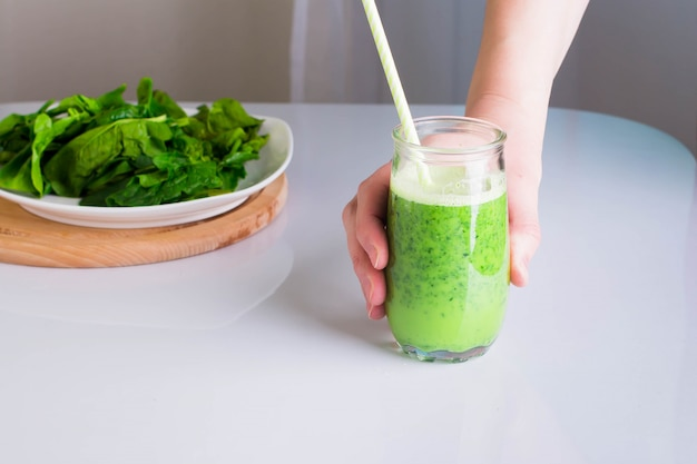 Woman hand with healthy drink smoothie from green spinach and apples. Premium Photo