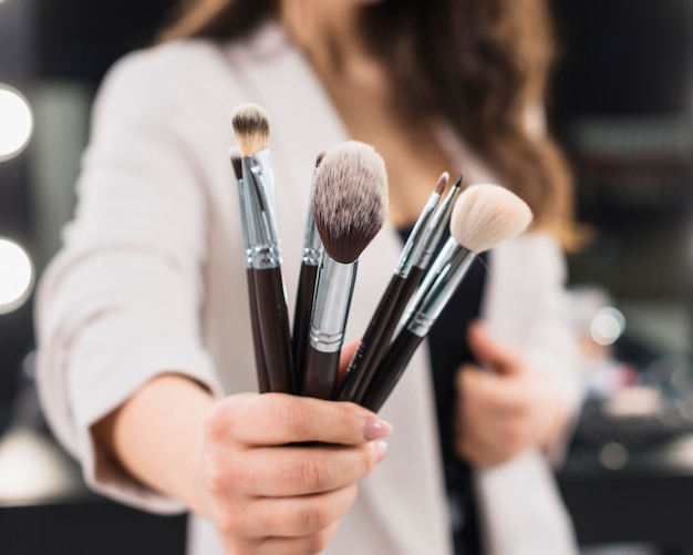 Woman hand with makeup brushes Free Photo