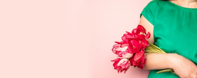 Woman hand with manicure holding tulips flowers on pink background Premium Photo
