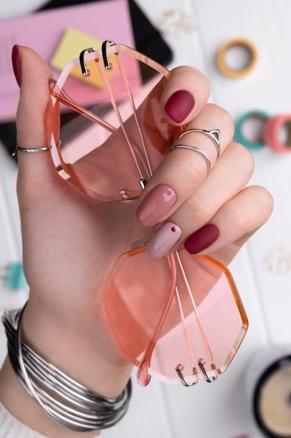 최소한의 분홍색 봄 여름 매니큐어 디자인 들고 선글라스와 여자 손 프리미엄 사진