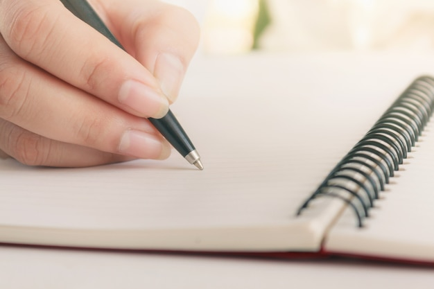 Woman hand with pen writing on notebook Premium Photo