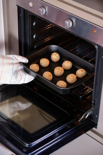 Woman hand with pot catching metal baking sheet with cheese bread from oven. cheese buns.. Premium Photo