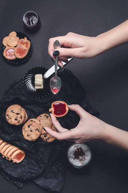 ジャムとビスケットのスプーンで一杯のコーヒーまたはカプチーノと黒いテーブルの背景にチョコレートクッキーの女性手。 Premium写真