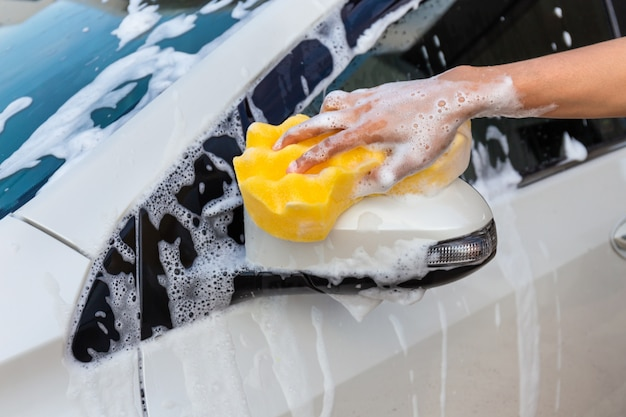 Woman hand with yellow sponge washing side mirror modern car or cleaning automobile. Premium Photo