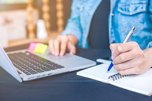 Woman hand works in a laptop computer and is writing on notepad ...