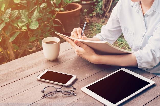 Женщина руки, писать книгу и телефон, таблетка на столе в саду в кафе с  урожай тонированное. | Премиум Фото