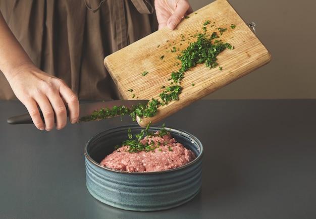 여자 손은 오래 된 나무 테이블에 아름다운 세라믹 그릇에 다진 고기에 신선한 녹색 파슬리를 추가 무료 사진