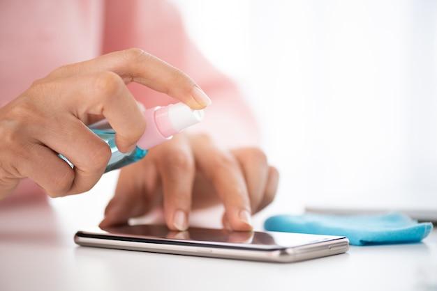 Женские руки чистят экран смартфона волокнистой тканью от грязной пыли и вирусов Premium Фотографии