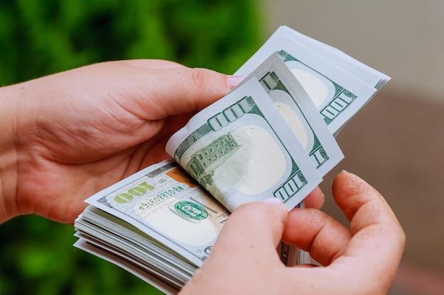 Руки женщины, считая банкноты доллара сша. считать или потратить деньги. Premium Фотографии