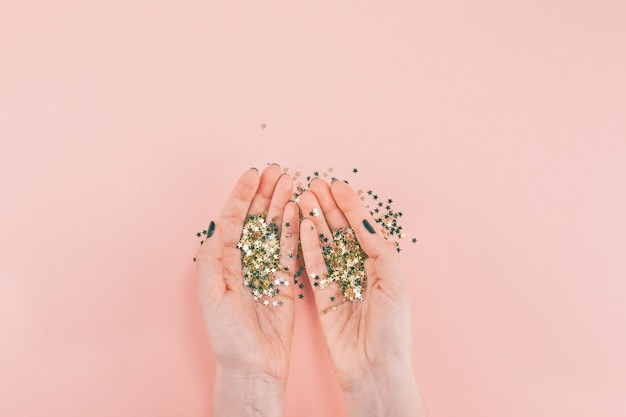 Woman hands covered golden stars confetti on pink Premium Photo
