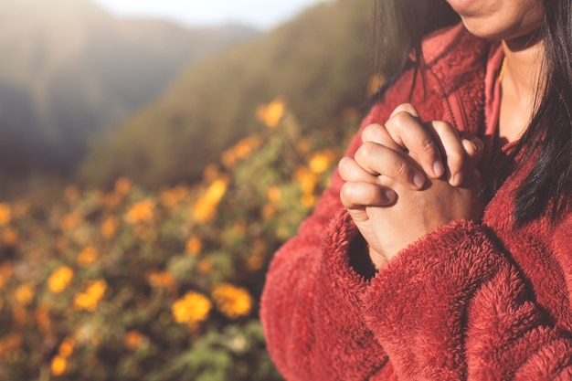 Woman hands folded in prayer in beautiful nature background with sunlight in vintage color tone Premium Photo